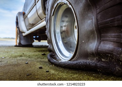 Damaged flat offroad tire on a road