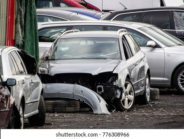 Damaged grey cars waiting in a wreckyard to be recycled or used for spare parts