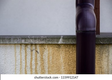 damaged gutter and damp patches on the house wall