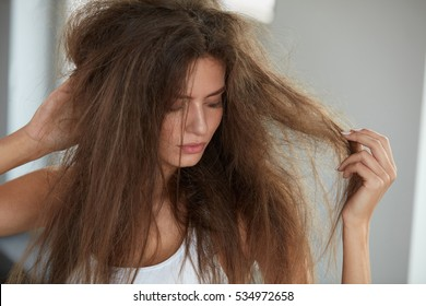 Damaged Hair. Beautiful Sad Young Woman With Long Disheveled Hair. Closeup Portrait Of Female Model Holding Messy Unbrushed Dry Hair In Hands. Hair Damage, Health And Beauty Concept. High Resolution