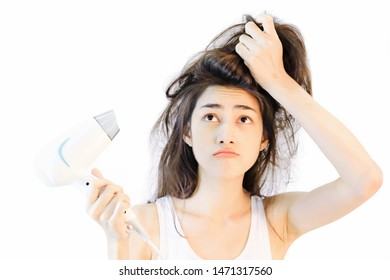 Damaged hair,Young beautiful asian woman Wearing a white tank top, Long black hair, Using a hair dryer She is quite uncomfortable with the dry, split ends.