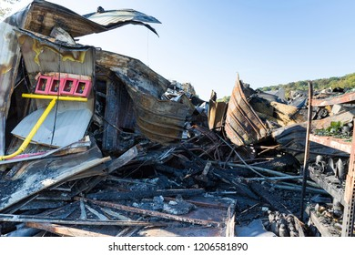 Damaged industry supermarket after arson fire with burn debris of twisted metal wood structure after intense burning fire disaster ruins waiting for investigation for insurance