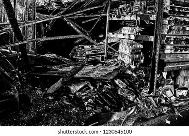 Damaged industry supermarket after arson fire with burn debris of twisted metallic wood structure after intense burning fire disaster ruins waiting for investigation for insurance. Black and white