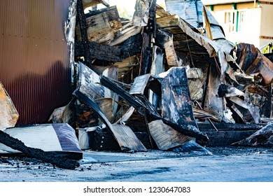Damaged industry supermarket after arson fire with burn debris of twisted metallic wood structure after intense burning fire disaster ruins waiting for investigation for insurance. Saturated contrast