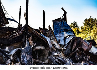 Damaged industry supermarket after arson fire with burn debris of twisted metallic wood structure after intense burning fire disaster ruins waiting for investigation for insurance. Saturated contrasts