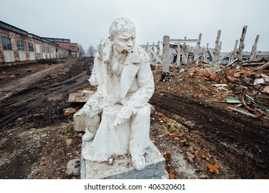 Damaged Lenin statue sitting on a chair with a book in his hand. peeling vintage paint. ruins of the factory background. The concept of system failure
