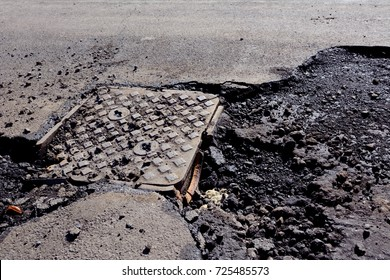 Damaged manhole cover on a road with broken asphalt, undergoing street repairs