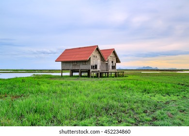 Damaged Old Two Red Roof Huts on The Green Field with the Blue Sky at Thalesap Songkhla and Thale Noi Waterfowl Reserve Park in Phatthalung ,Thailand