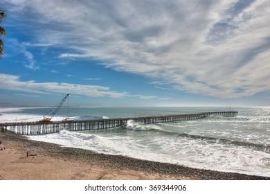 Damaged pier under repair as large waves hit.