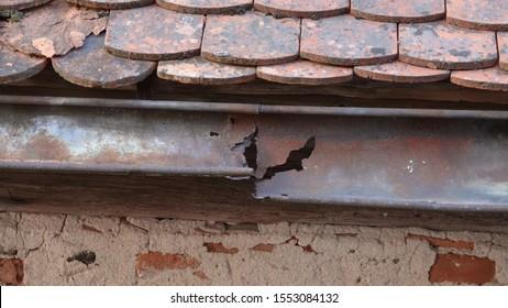 Damaged rain gutter on old tile roof
