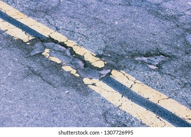 Damaged roadway of Yokohl Drive in California, USA - cracked asphalt blacktop with potholes and patches.