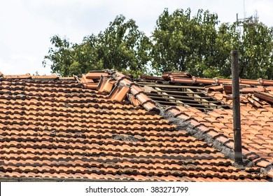 Damaged roof construction on house needs tiles or shingles repaired and replaced
