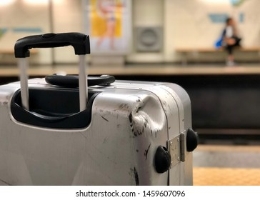 Damaged silver suitcase standing on the platform at a railway station