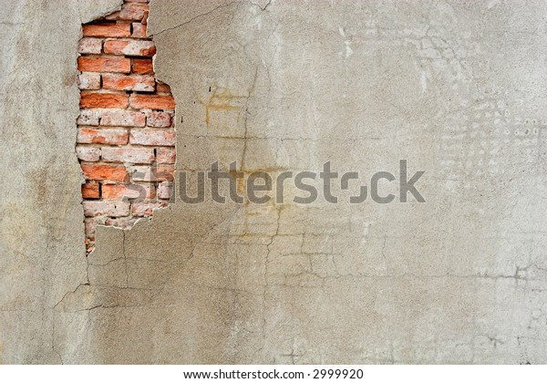 A damaged stucco wall with original brick exposed.