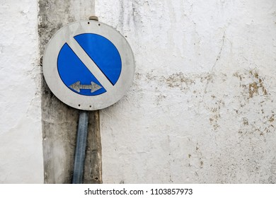 damaged traffic sign against decayed wall