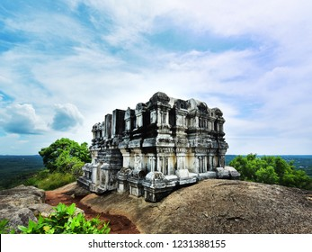 The damaged vimana of the Chitharal Jain cave temple (Chitharal Malai Kovil),Thiruchanattu hill, Chitharal village in Kanyakumari, Tamil Nadu, India, against cloudy blue sky.