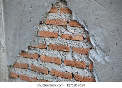 Damaged wall of an old barely standing building. Old wall surface is ruptured by time