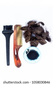 Damaged and white female hairs with an black hair coloring brush and a bowl of hair dye with a comb concept of dying the hairs isolated on white.