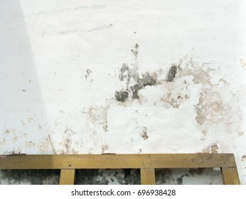 Damaged white wall and wooden fence on the bottom