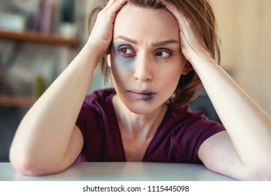 Damaged woman. Young beautiful woman feeling extremely frightened having damaged face after unexpected home violence