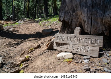 Damaged wooden sign indicating unrestricted camping beyond this point
