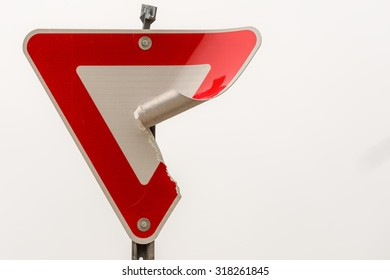 Damaged yield sign against a cloudy winter sky. The curled back is scratched and dirty; lines that reflect headlights back in the same direction can be seen under the diamond pattern on the front.
