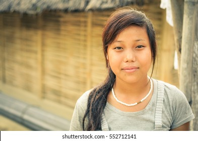 Damak, Nepal - circa May 2012: Young woman with long hair wears white shirt and necklace made of white beads at Nepali refugee camp in Damak, Nepal. Documentary editorial.