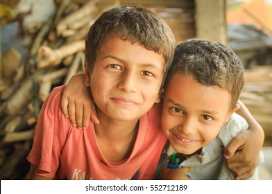 Damak, Nepal - circa May 2012: Two young brothers with brown eyes hug and smile to photocamera at Nepali refugee camp in Damak, Nepal. Documentary editorial.