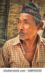Damak, Nepal - circa May 2012: Old man with moustache wears checked shirt and cap on his head and looks to left at Nepali refugee camp in Damak, Nepal. Documentary editorial.