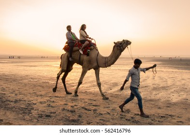 Daman, India - January 7, 2017 : Unidentified tourist couple enjoying the camel ride at the Jampore beach.