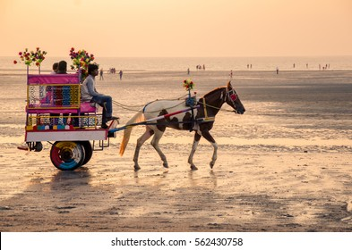 Daman, India - January 7, 2017 : Indian coachman with his Horse carriage along with passengers/tourists at Jampore Beach.