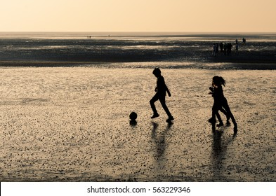 Daman, India - January 7, 2017 : A beautiful silhouette of children playing football during sun set at the beach.