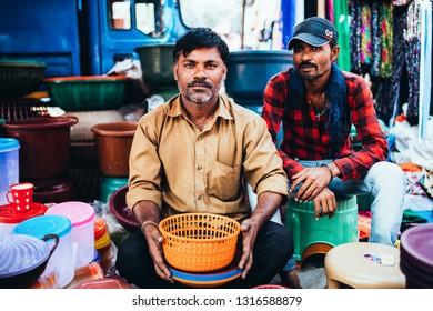 DAMAN MARKET PLACE, INDIA - November 28, 2017: Men sit in their pot stall.