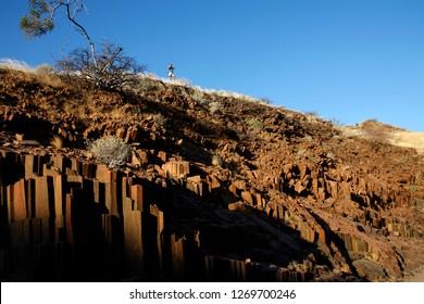 Damaraland. Namibia. 06.12.09. An adventure tourist near the 'Organ Pipes' landmark, a basalt rock formation in Damaraland, Namibia.
