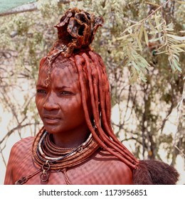 DAMARALAND, NAMIBIA, AFRICA - October 15, 2016. Portrait of a beautiful young woman of the Himba tribe with traditional hairstyle and necklaces in desert.