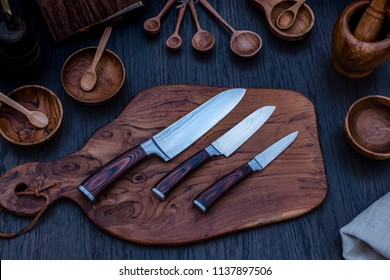 Damascus kitchen steel Knives on Wooden kitchen cutting Board. Kitchen Utensils background with Santoku Japanese knife damascus steel blade knife. Japanese knife made of Damascus steel