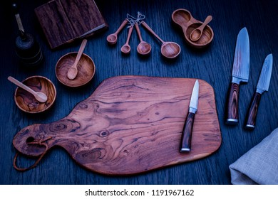 Damascus kitchen steel Knives, Wooden kitchen cutting Board, wooden kitchen measuring spoons, Recipe Book. Kitchen Utensils background with Santoku damascus steel blade knife