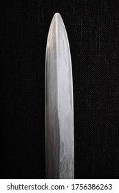 Damascus steel saber blade close up on a black background