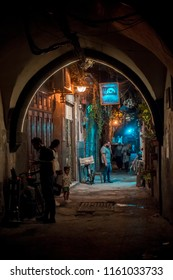 Damascus / Syria - 25/07/2018: night photo of a narrow alley in the old city near the Umayyad Mosque in Bab Touma, Al Qaymariyya and Bab Sharqi with people walking under the street lights.