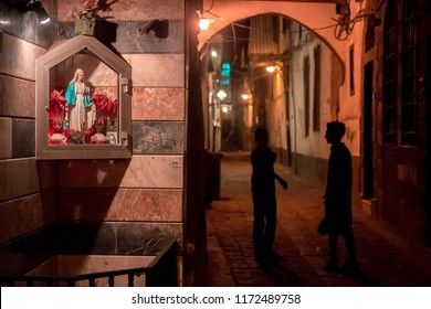 Damascus / Syria - 25/07/2018: night photo of a narrow alley in the old city near the Umayyad Mosque in Bab Touma, Al Qaymariyya and Bab Sharqi with kids walking under the street lights.