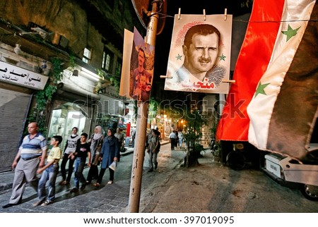 Damascus,Syria - August 04,2010 : Pre-war Syria.A poster of Syrian president Bashar al-Assad hangs in front of a shop in the old city of Damascus.Syrian flags.The number of Syrians who fled the Civil