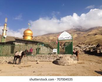 DAMAVAND MOUNTAIN, IRAN - October 2016:  Mosque with golden roof underneath volcano Damavand in Iran. Horses near the small mosque on Damavand mountain, Iran