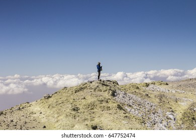 Damavand mountain, Iran - October 2016:Young woman standing on the top of Damavand volcano- the highest mountain of Iran