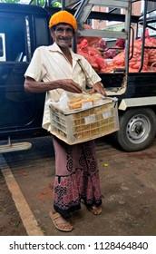 Dambulla, Sri Lanka, April 4, 2018 - Smiling old Sri Lankan snack vendor at Dambulla Dedicated Economic Center, a wholesale fruit and vegetable market.