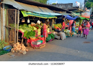 Dambulla, Sri Lanka - April 4, 2018: Greengrocer shop on the main road of Dambulla in the warm light of an end of afternoon.