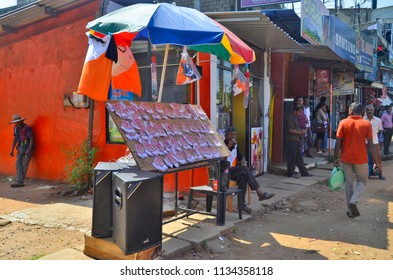 Dambulla, Sri Lanka - April 4, 2018: Lottery tickets vendor under an umbrella promoting his business with his public address system on the main road of Dambulla.