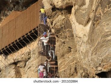 DAMBULLA, SRI LANKA - FEBRUARY 14: People climbing the stairs on the rock face of Sigiriya Rock or Lion Rock, a World Heritage Site near Dambulla, Sri Lanka on the 14th February, 2014.