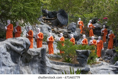 DAMBULLA, SRI LANKA - JULY 28, 2012 : A line of Buddhist monk statues approaching the The Golden Temple at Dambulla in central Sri Lanka.