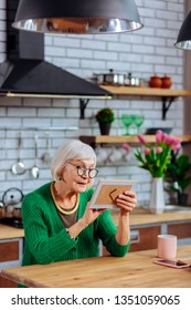 Dame blandly palming photo. Photo of charming silver-haired septuagenarian dame wearing glasses and trendy emerald cardigan sitting at kitchen and blandly palming photo frame