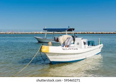 Dammam, Saudi Arabia, January 7th, 2017, An Arabian fisherman tying yacht rope at the beach with background of sea in the corniche park, the city of Dammam, Kingdom of Saudi Arabia.
